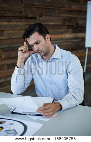 Tensed male graphic designer looking at photos in office