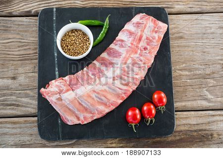 Raw beef ribs, chillies, cherry tomatoes and coriander seeds on slate board