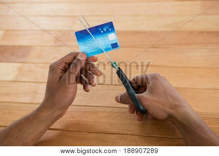 Hand of businessman cutting credit card with scissors