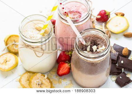 Set of milkshake in jars. Banana chocolate and strawberry milkshakes with nuts and coconut. Summer dessert. Healthy food on white.