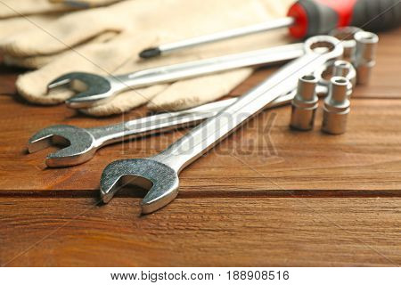 Setting of tools for car repair and gloves on wooden background