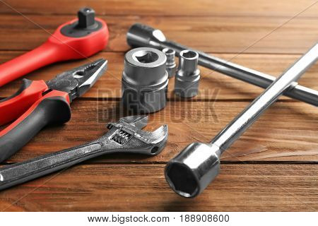 Setting of tools for car repair on wooden background
