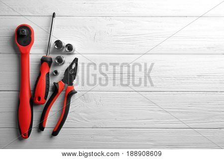 Setting of tools for car repair on white wooden background