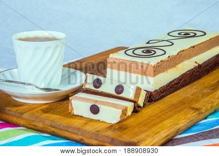 Holiday cake Three-colate. Professional bakery. Three-layer chocolate cake, decorated with chocolate patterns. Background - porcelain cup with hot tea