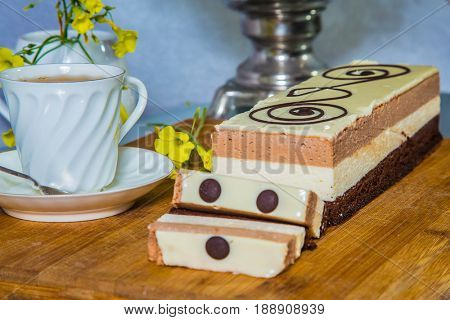 Cake Three-colate. Three-layer chocolate cake, decorated with chocolate patterns. Background - white vase with flowers and porcelain cup with hot tea. Professional bakery