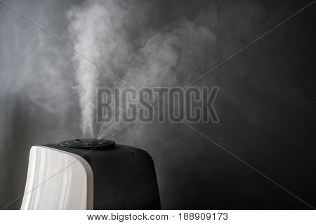 humidifier distributes steam in the living room against the background of a black chalkboard.