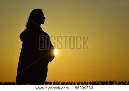 The stunning silhouette of a pregnant woman as the sun slowly creeps past her bump at dusk.