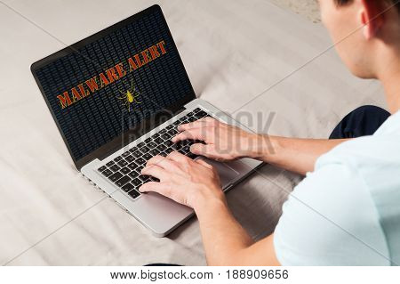 Man surprised by malware alert while uses a laptop computer.
