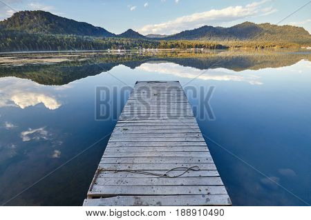 Pier on the lake on the background of sunset in a clear summer day. Warm summer evening on the dock. Fabulous views of the lake and the bridge in the sunlight