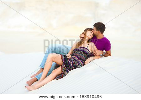 Lovers kissing on the barkhan. romantic travel honeymoon vacation summer holidays. young girl dressed in a colorful dress and man in a violet t-shirt. they embracing outdoors