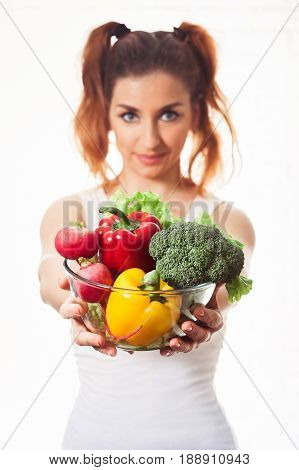 Beautiful caucasian girl holding glasses bowl with ingredients for low-caloric vegetables salad. Isolated on white background