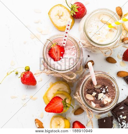 Set of milkshake in jars. Banana chocolate and strawberry milkshakes with nuts and coconut. Healthy food. Top view on white.