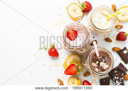 Set of milkshake in jars. Banana chocolate and strawberry milkshakes with nuts and coconut. Summer dessert. Healthy food. Top view on white.