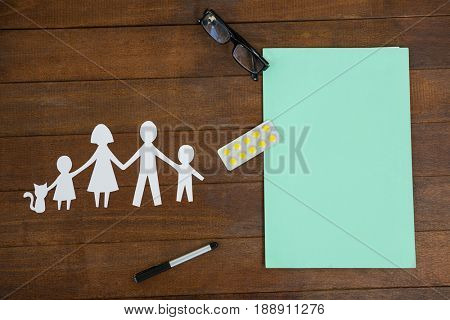Paper cut out family chain with medicine and spectacles on table