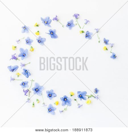Wreath made of bellflower pansy flowers and yellow flowers on white background. Flat lay top view