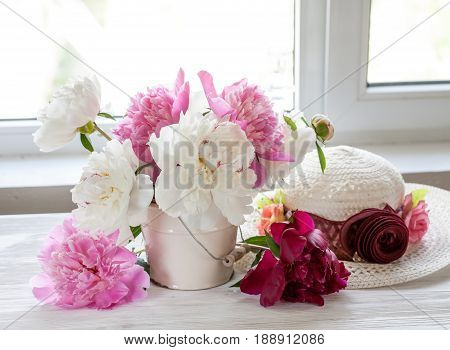 still life with peonies and white hat on the window