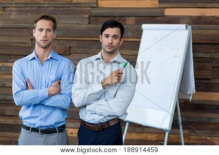 Two male business executives in a meeting standing in front of a flip chart at office