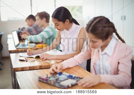 Portrait of smiling schoolgirl doing homework in classroom at school