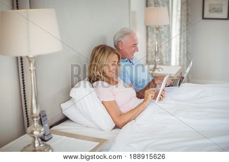 Happy senior couple on bed using laptop and digital tablet in bedroom