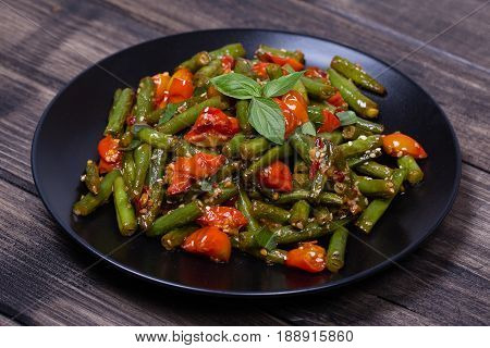 Cooked green beans red cherry tomato with sesame seeds in black plate close up