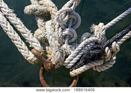 Rusted mooring ring with naval knots ropes on the pier