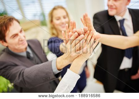 Hands of business people giving a high five to each other as sign of happines for the success