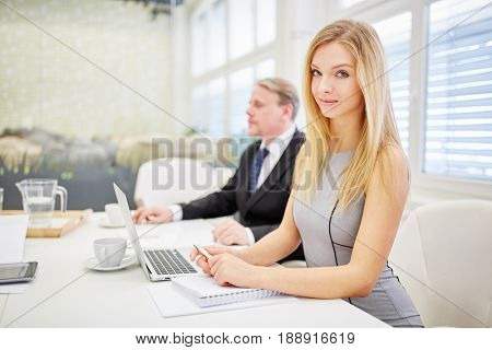Businesswoman with laptop computer in conference room with consultant people