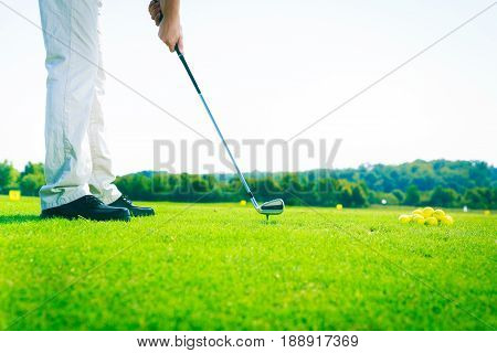 a golf player is practicing on the driving range