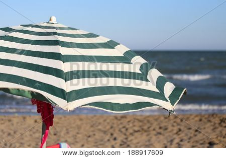 Large Sun Parasol On The Shore Of The Ocean In The Hot Summer Su
