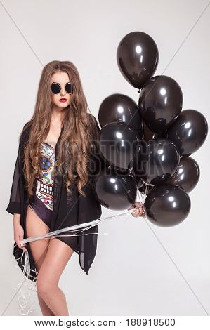 Sexy girl in cimbination and glasses standing on a white backgroung and holding a bundle of baloons.
