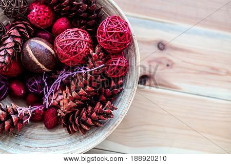 Wooden decoration plate with rattan balls and pine cones. Top view. Close-up