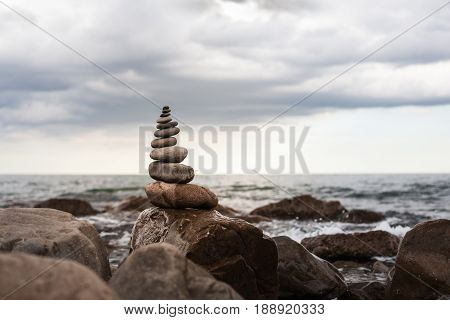 Pyramid Of Stones On A Background Sea Of Large Stones And Water