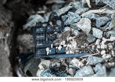 broken black keyboard lying on the gabage under the stone