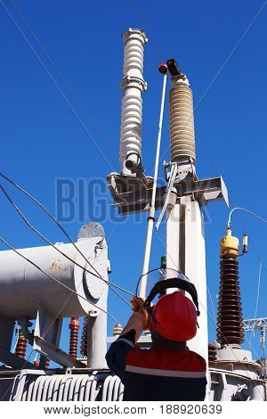 VOLGOGRAD RUSSIA - April 27 2017: The duty electrician of power transformer substation in overalls and a protective helmet makes expeditious switchings