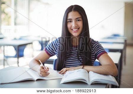 Schoolgirl doing homework in classroom at school