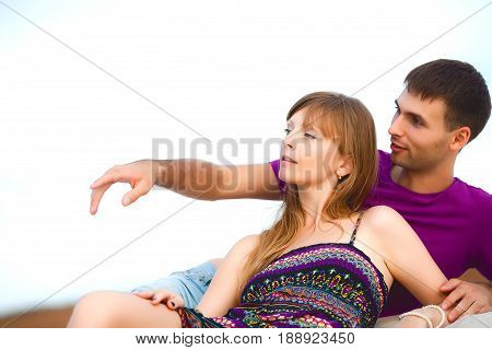Lovers lying on the beach in desert. romantic travel honeymoon vacation summer holidays. young girl dressed in a colorful dress and man in a violet t-shirt. man points at something with his finger