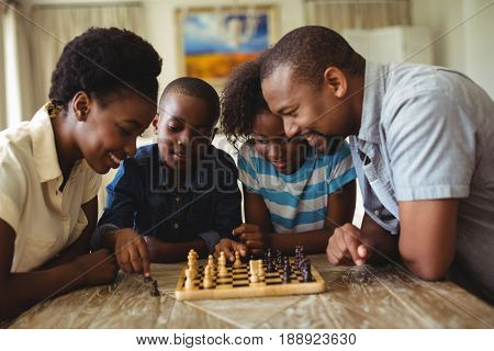 Family playing chess together at home in the living room at home
