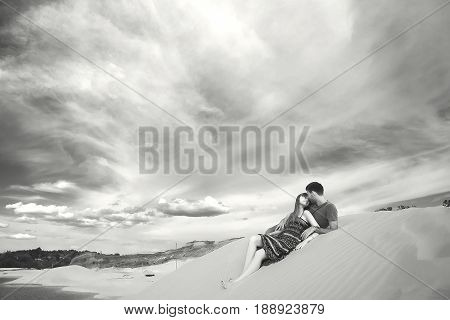 man and woman on the barkhan. romantic travel honeymoon vacation summer holidays. young girl dressed in a colorful dress and man in a violet t-shirt. they embracing outdoors. black white tone