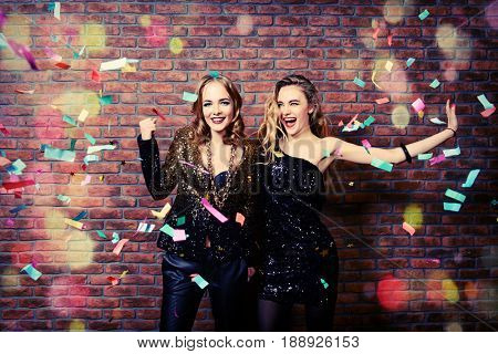 Modern girls having fun on a night party. Celebration, confetti. Christmas party.