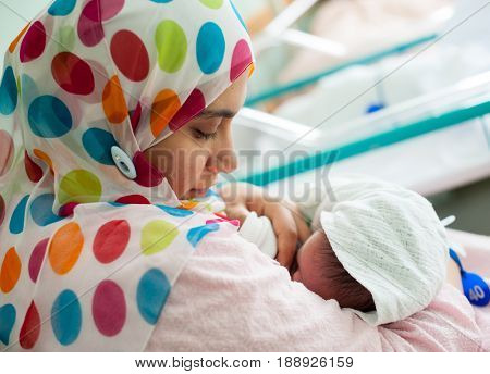 muslim woman feeding her new born baby from her breast
