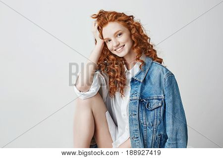 Young beautiful foxy girl smiling looking at camera posing over white background.