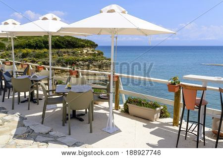 Restaurant furniture with umbrella with magnificent view of the cliffs near Sidari - Corfu island in Greece.