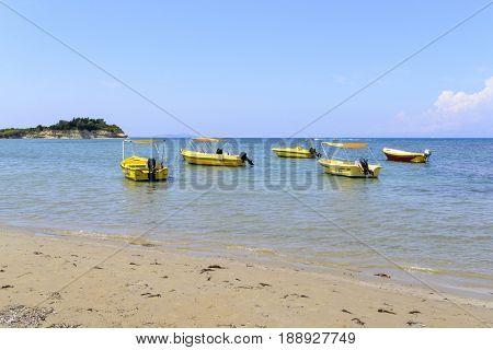 Boats on the sea waiting to be hired by tourists near Sidari - Corfu island in Greece.