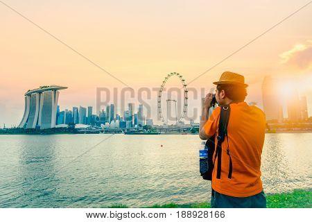 Photographer or traveller using a professional DSLR camera take photo beautiful sunrise time at Singapore City Singapor