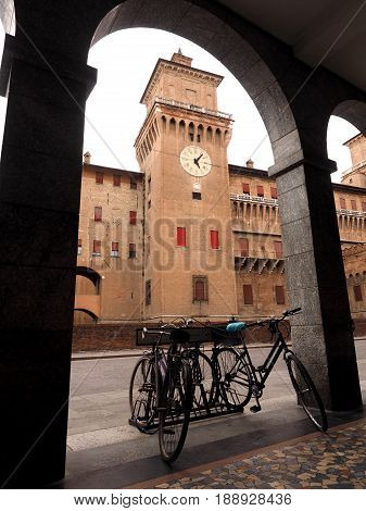 Ferrara, Italy. Castle, tower with the clock seen from the porticoes of the municipal theater