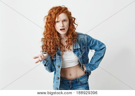 Displeased young brutal redhead girl looking at camera not understanding over white background. Copy space.
