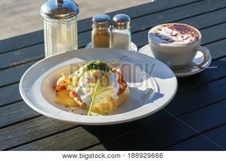 Delicious Eggs Benedict served on white plate on wooden table