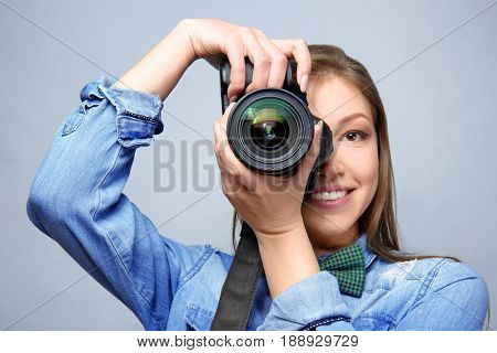 Beautiful young photographer on light background