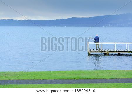 Old man standing on the bridge at Lake Taupo South Island of New Zealand