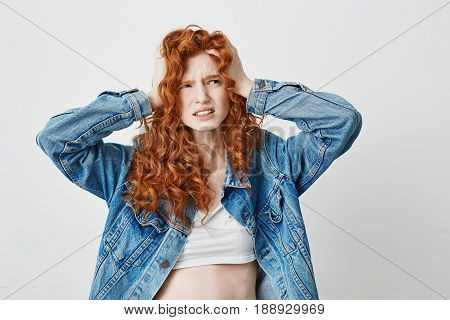 Displeased young cool redhead girl grasping clutching at head over white background. Copy space.